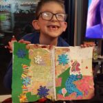 Young boy with a big smile, showing his artwork he created.