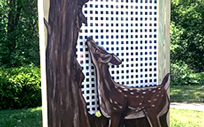 02 - Captured Moments - A sculpture of a 2 dimensional deer standing below the shade of a tree. Behind sits a display of 100's of 1 by 1 inch photo negatives depicting the artist's life of her Grandmother.
